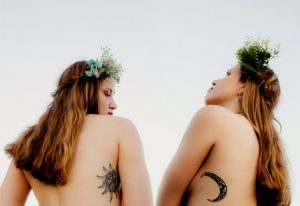twin sisters look at each other with ying and yang symbol tattoos