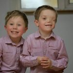 Oliver and Harry give a cheeky smile to the camera wearing matching pink shirts