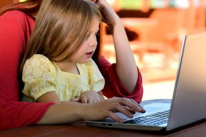 A young girl sits, typing onto a laptop with her mother behind her