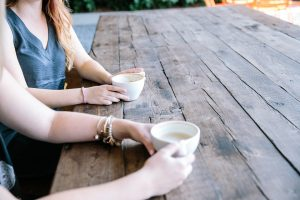 Two women sit enjoying a coffee. We can only see their hands and coffee cups