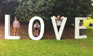 Autism, love and Life ~ All the children stand within a huge letter which spells the word LOVE