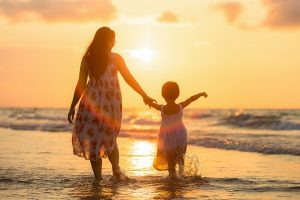 being a parent ~ a mother and daughter walk along the beach in the sunset