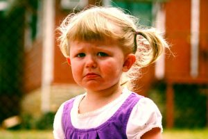 being a parent - a toddler girl has a dropped lip and a sad face