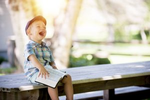being a parent - a young boy throws his head back laughing with a book open on his knee