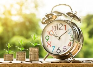 Financial plan - piles of money grow a sprout infront of a clock