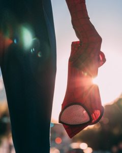 NHS heroes - a figure holds a spiderman mask at their side infront of beams of sunlight