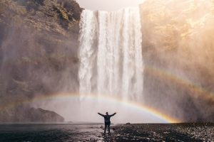 NHS heroes - a man stands before a waterfall, arms outstretched as a rainbow arches across it