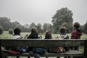 School holidays - a group of children sit on a park bench with their backs to the camera