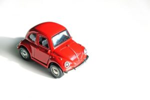 School holidays - a small toy red car sits on a white background