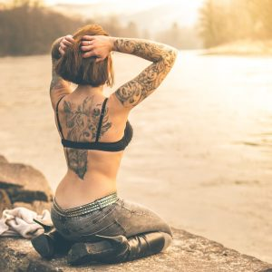 Tattoo or not tattoo - a woman faces a lake wearing jeans and a bra and showing her tattood back and arms
