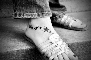 Tattoo or not tattoo - a womans foot has a few stars tattod on it