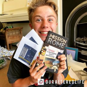 Visit rome - Oliver smiles massively as he shows his plane tickets and Rome guide book