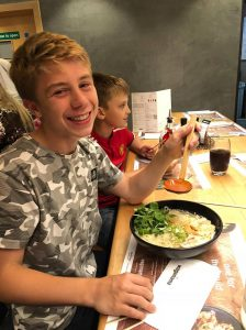 Young aviators day - Oliver smiles as he tucks into his chicken ramen