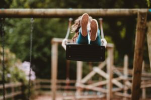 school holidays - a girl swings high showing the soles of her trainers