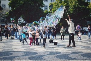 school holidays - children gather and giggle under a stream of bubbles being blown by a big frame