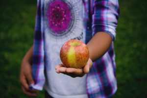 why i left teaching - a boy holds an apple out infront of him