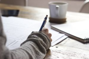 why i left teaching - a woman writes loads of notes with a coffee cup blurred infront of her