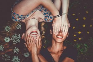 world friendship day - two friends lie next to each other covering each others eyes