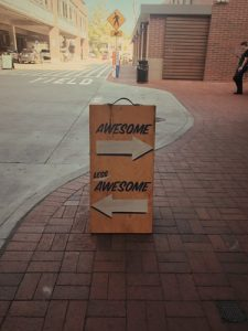 left handed - a sign shows arrows pointing right with 'awesome' and left with 'less awesome'