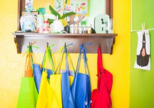 Working when your child has additional needs - bright aprons hang up at a school club