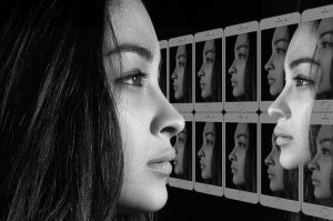 a woman looks at photscreens full of her own reflection
