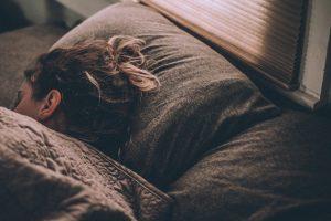 a woman sleeps under blankets
