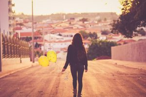 a woman walks away holding a couple of balloons