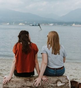 two friends sit on a stone chatting as they look out to sea