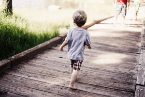 A boy walks across a bridge