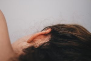 A woman lies on her side facing away so we can see her ear