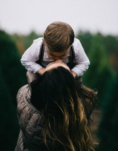 lip kiss - a woman holds her son up and kisses him