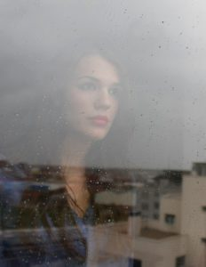 postnatal depression symptoms and support - a woman looks out over a landscape reflected in a window