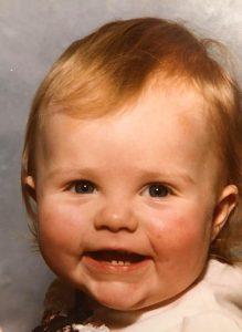 me as a toddler, smiling at the camera