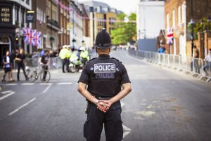 a police officer stands with his hands behind his back looking on to a street