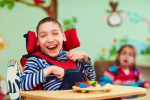 a disabled boy smiles in his wheelchair at a support centre