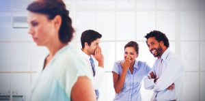 workplace bullying with colleagues sniggering and whispering behind a womans back