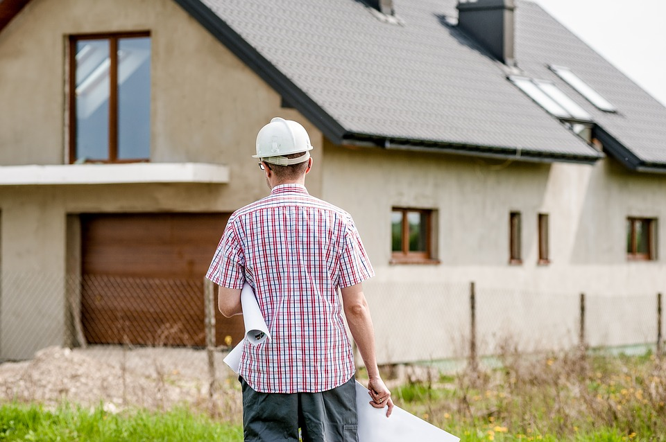 a builder walks towards a house with plans under his arm