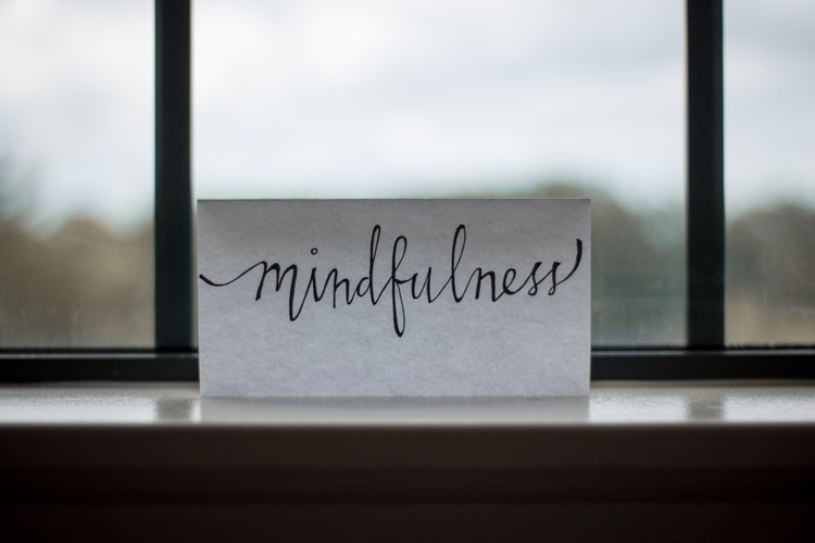 a simple white note in a windowsill says mindfulness