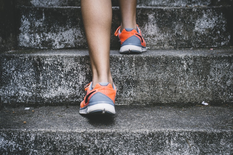 a woman climbs steps in grey and orange trainers