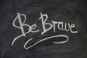 be brave is written on a board in chalk