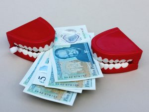 Life after Divorce - Two sets of false teeth are biting a wad of bank notes
