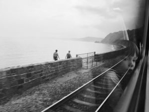 The reflection of a child in the train window as they pass a couple walking on the beach