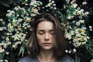 Respite: A woman lies in a bed of daisies