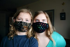 anxious about face masks - a mother and daughter wear their masks at home