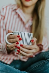 A woman with red nails holds a stripy mug